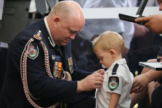 RFS Commissioner Shane Fitzsimmons pins the posthumous service medal of Geoffrey Keaton onto his son, Harvey. Geoffrey died fighting bushfires in December.