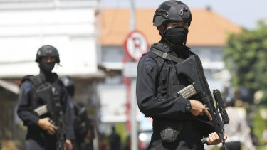 Officers stand guard outside the local police headquarters following an attack in Surabaya, East Java, Indonesia, on Monday.