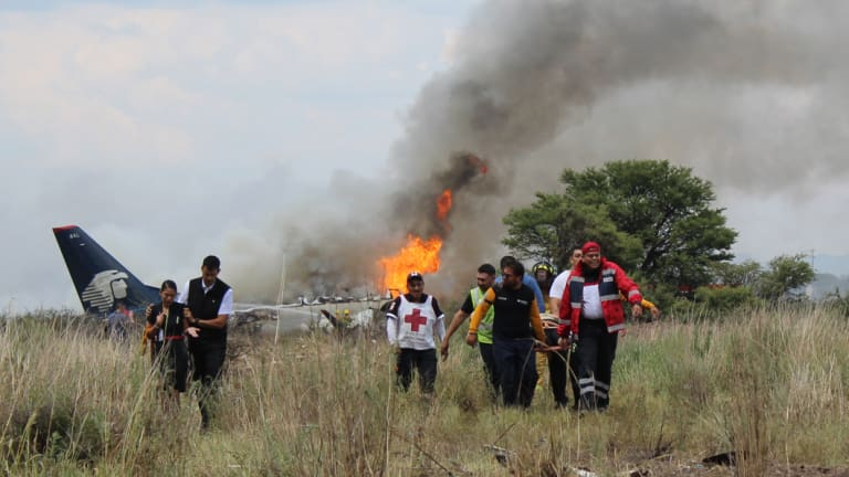 Airline workers, left, walk away from the site where an Aeromexico airliner crashed in a field near the airport in Durango, Mexico.