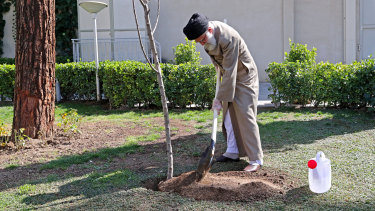 Supreme Leader Ayatollah Ali Khamenei, wearing gloves, participates in a tree planting ceremony in Tehran, Iran.