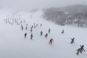 Hundreds of skiers and snowboarders walk up the mountain after a blizzard shuts down the chairlifts at the Snowy Mountains on Sunday.