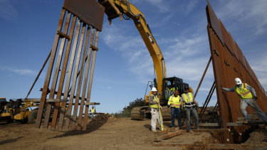 Construction workers install new border wall sections seen from Tijuana, Mexico, in January.