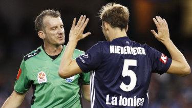 The referee prepares to show Georg Niedermeier a red card.