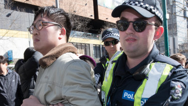 Police remove a Chinese nationalist from a Melbourne rally in support of Hong Kong democracy protesters.
