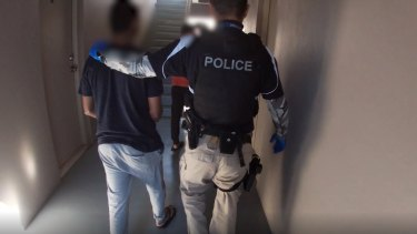 The two foreign students were led out of their Albion accommodation in handcuffs on Tuesday.