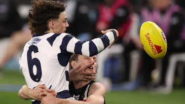 Geelong's Jordan Clark is tackled by Pie Chris Mayne. Clark dislocated his shoulder during the match.