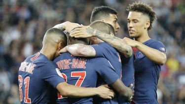 PSG players, with Notre Dame on the back of their jerseys, celebrate after Kylian Mbappe scored.