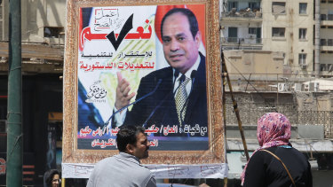 People walk past a banner supporting proposed amendments to the Egyptian constitution with a poster of Egyptian President Abdel-Fattah el-Sisi in Cairo.