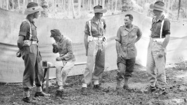 Sgt Major Tsuruo Sugino (seated) eats lunch as two provost guards talk to Warrant Officer Warrant Sticpewich, one of six survivors of Sandakan, at Labuan, Malaysian Borneo.