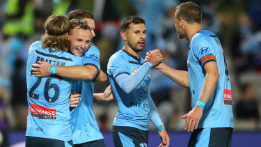 Sydney FC celebrate their second and decisive goal, though Kosta Barbarouses holds back against his former club.