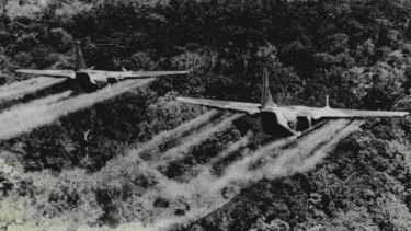 Two US Airforce C-123's fly low over heavy jungle spraying the canopy with defoliation liquid to defoliate Viet Cong base areas, crops and communication routes circa 1966.