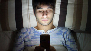 Man on phone in bed.