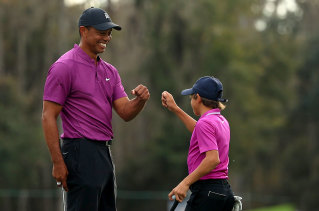 Tiger Woods and son Charlie Woods high five after a birdie on the ninth hole during the first round of the PNC Championship at the Ritz Carlton Golf Club on December 19, 2020 in Orlando, Florida.