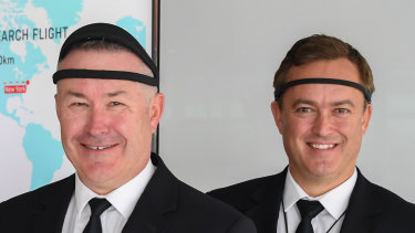 Qantas Captain Sean Golding (left) and first officer Jeremy Sutherland (right) wearing EEG monitoring headbands, which track brain waves to gauge levels of alertness and quality of sleep.