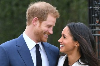 Prince Harry and Meghan Markle smile as they pose for the media in the grounds of Kensington Palace to announce their engagement.