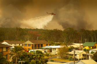 An Aircrane water bombing helicopter drops water on a bushfires in Harrington, 335 kilometres north-east of Sydney.