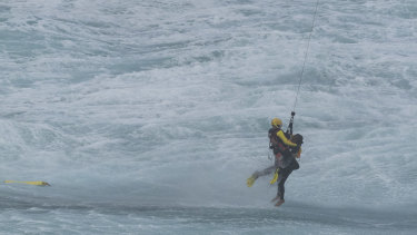The third surf lifesaver is winched from the water near Port Campbell on Sunday.