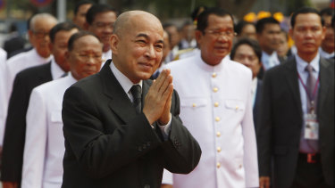 Cambodian King Norodom Sihamoni, foreground, greets his government officers in front of the National Assembly in Phnom Penh last week. Prime Minister Hun Sen is to his right inthe background.