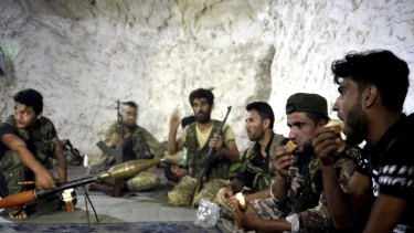 Fighters with the Free Syrian army eat in a cave where they live, on the outskirts of Idlib city, on Sunday.