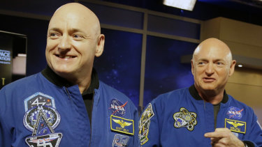 NASA astronaut Scott Kelly, left, and his identical twin, Mark, stand together before a news conference in Houston in 2014.