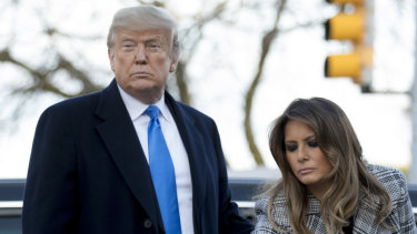 First lady Melania Trump, accompanied by President Donald Trump, puts down a white flower at a memorial for those killed at the Tree of Life Synagogue in Pittsburgh.