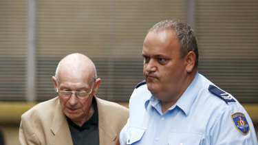 Roger Rogerson, left, is escorted out of Sydney's King Street courts in 2016.