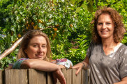 Belinda Jackson (left) and Jude van Daalen by the garden fence where they had meetings during the creation of their book about life under Covid restrictions.