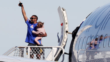 Liam Ryan, with his daughter in his arms, waved farewell when West Coast players and staff flew to the Gold Coast for the resumption of the AFL season.