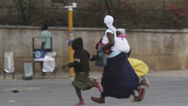 What appears to be a mother and children flee violence in Zimbabwe's capital.