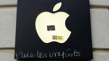 """Graffiti written on an Apple sign reading """"Pay your taxes"""", in front of an Apple store during a demonstration on Saturday in Lille, Northern France."""