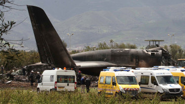Firefighters and civil security officers work at the scene of a fatal military plane crash in Boufarik.