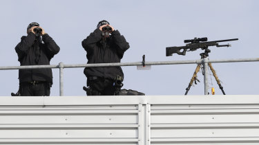 Police marksmen scan the area as they await the arrival of President Donald Trump and first lady Melania Trump at Stansted Airport in England.