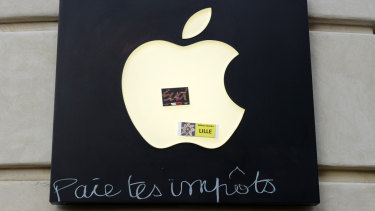 "Graffiti written on an Apple sign reading ""Pay your taxes"", in front of an Apple store during a demonstration on Saturday in Lille, Northern France."