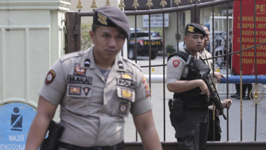 Police officers stand guard at the gate of the local police headquarters following a suicide bombing attack at the compound in Medan, North Sumatra, on Wednesday.