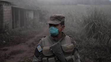 """A soldier stands guard at a search and rescue site near the Volcan de Fuego, or """"Volcano of Fire,"""" in Escuintla, Guatemala."""