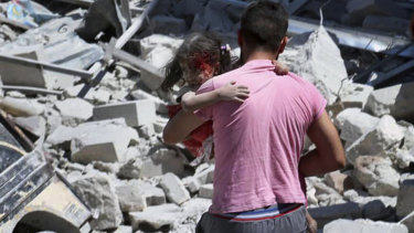A Syrian man carries an injured girl after an air strike hit an open-air market in Ariha, Idlib province, in July, killing several people.