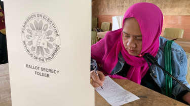 A Muslim woman votes in a referendum at the Marawi Sagonsongan elementary school polling station in Marawi.