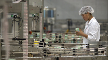A worker monitors a milk production line at an Inner Mongolia Yili Industrial Group Co. factory in Hohhot, Inner Mongolia.
