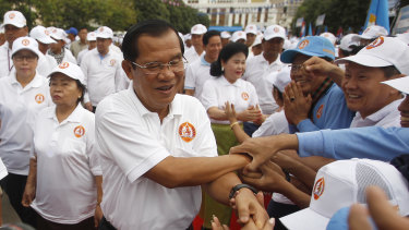 Cambodian Prime Minister Hun Sen, centre, greets supporters on arrival for his Cambodian People's Party's campaign in Phnom Penh.