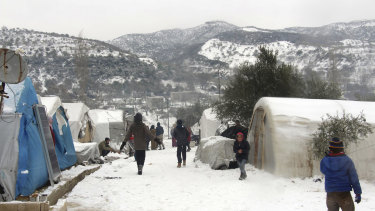 Syrians walking outside their tents at a displaced people camp near Turkish border, in Idlib province, Syria.