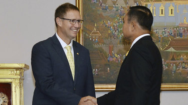 Richard Harris shakes hands with Thailand's Prime Minister Prayuth Chan-ocha after receiving the Member of the Most Admirable Order of the Direkgunabhorn.