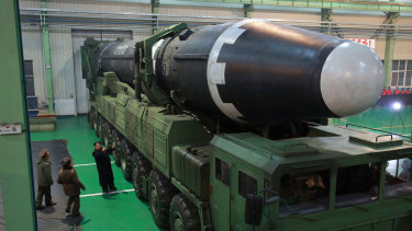 North Korean leader Kim Jong-un, third from left, and what the North Korean government calls the Hwasong-15 intercontinental ballistic missile, in North Korea.