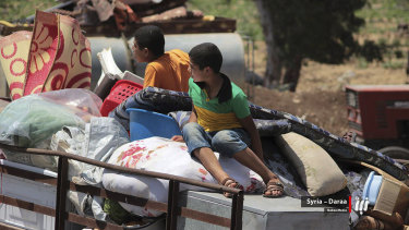 Children with their family belongings in the back of a truck fleeing from Daraa, southern Syria.