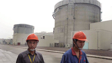 Workers walk past Qinshan No. 2 Nuclear Power Plant, China's first self-designed and self-built national commercial nuclear power plant in 2005.