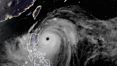 A satellite image with land graphic borders shows the width and trajectory of Mangkhut as it approached the Philippines.