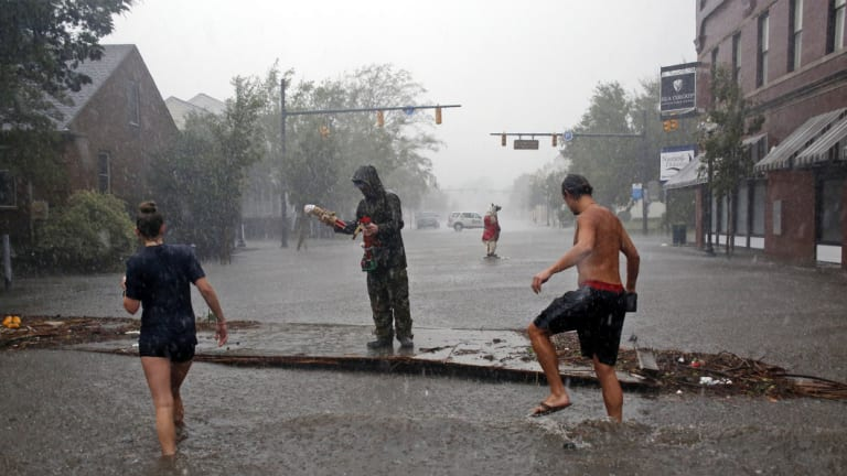 People survey the damage on Front Street in downtown New Bern, North Carolina.