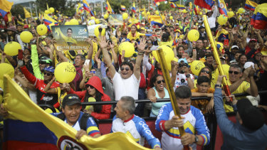Hometown hero: Fans in Zipaquira celebrate as they watch a giant screen broadcasting Bernal winning the Tour de France.