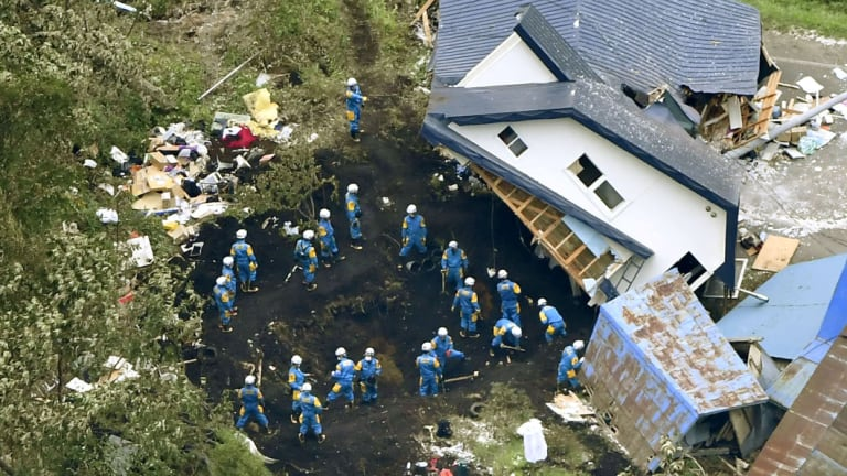 Police search for missing people around houses destroyed by an earthquake in Atsuma town, Hokkaido, southern Japan, on Friday,