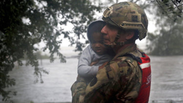 Rescue team member Sergeant Nick Muhar, from the North Carolina National Guard 1/120th battalion, evacuates a young child.