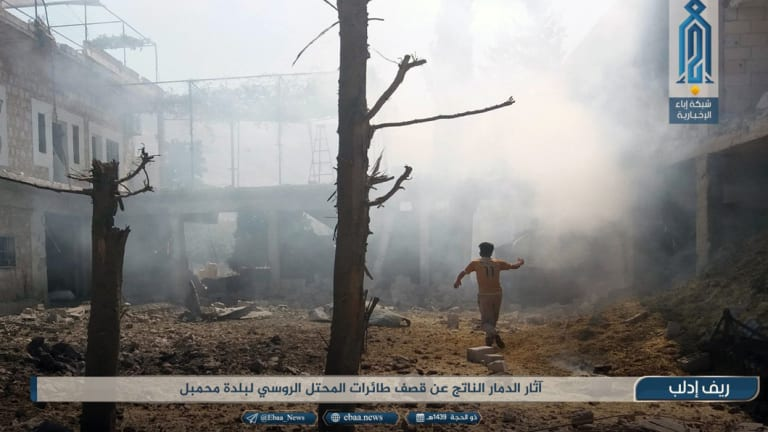 "An al-Qaeda affiliated video channel shows a man running as smoke rises over buildings hit by air strikes in Idlib province, Syria, last week. Arabic reads, ""Destruction from the strikes of the Russian occupation planes in Mahambal town."""
